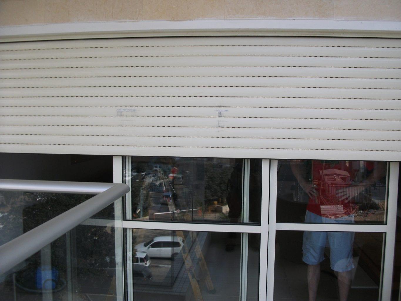 תמונה של תריסים חשמליים שלבי אלומיניום משוכים,מעקה זכוכית ופרופיל אלומיניום מעל.