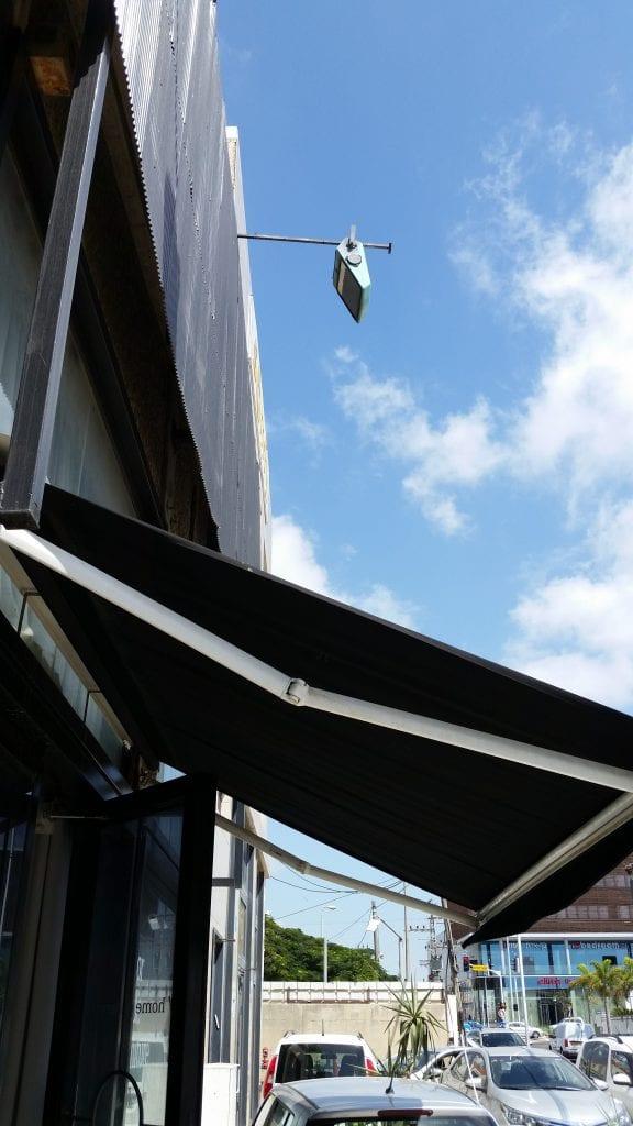 תמונה של סוכך זרועות חשמלי פתוח על רקע השמיים.למנוע נזקי קרני השמש החמות .להכניס אור וצבע לתוך הבית בקיץ החמים על פי תחזית מזג האוויר ניתן להתקין מגן רעידות ובקר חום לסגירה ופתיחה של הסוכך